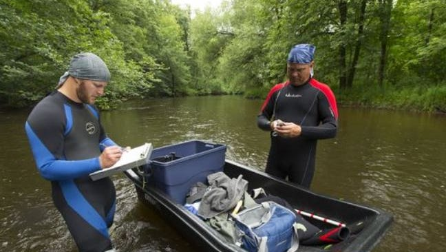 DNR staff conduct a survey for mussels in the Plover River near Stevens Point. A legislator wants to split the agency's wildlife and environmental functions