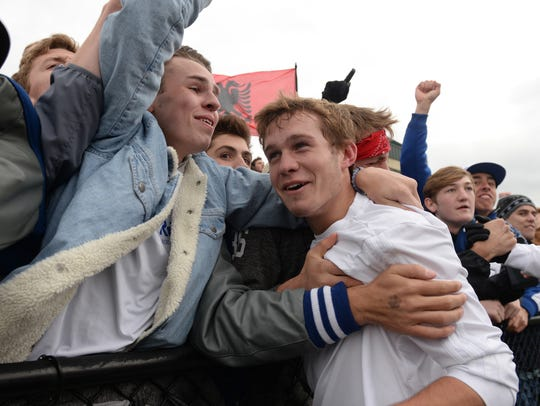 Detroit Catholic Central's Ryan Pierson is mobbed by