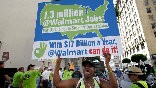 A women chants slogans at a protest against Walmart last y ear in Los Angeles. Walmart workers and supporters took part in a nationwide day of protests calling for better jobs and higher wages.