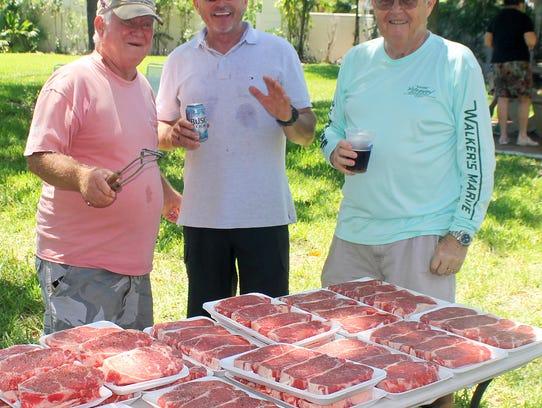 John Baker, Ron Linn and Ed Vesely prepare steaks for