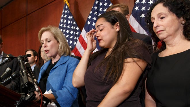 Anna, center, a survivor of sexual assault, with her mother, right, joins Sen. Kirsten Gillibrand, D-N.Y., left, during a news conference on Capitol Hill in Washington, Wednesday, July 30, 2014, to discuss legislation before the Senate.