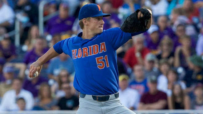 Florida Gators pitcher Brady Singer (51) throws against the LSU Tigers in the first inning in game one of the championship series of the 2017 College World Series at TD Ameritrade Park Omaha.