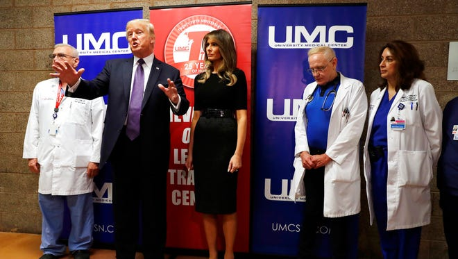 President Donald Trump talks as first lady Melania Trump and surgeon Dr. John Fildes, left, listens at the University Medical Center after Trump met with survivors of the mass shooting Wednesday, Oct. 4, 2017, in Las Vegas.
