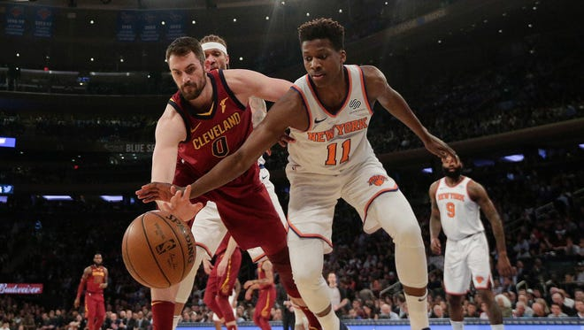 Cleveland Cavaliers center Kevin Love (0) and New York Knicks guard Frank Ntilikina (11) scramble for a rebound during the first quarter of an NBA basketball game, Monday, April 9, 2018, in New York.