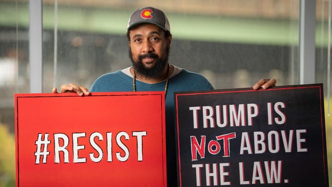 Reggie Hubbard of MoveOn displays signs the group has prepared for nationwide protests should President Trump take action to thwart special counsel Robert Mueller's investigation.