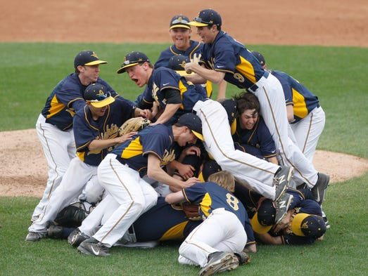 Pittsford Sutherland players pile on starting pitcher Michael VanderZwaag after the final out giving them the Section V Class A baseball final win over Brighton 5-4.