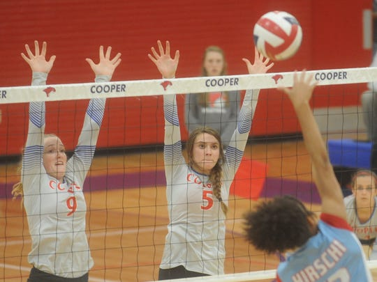Cooper's Caylee Collier (9) and Haley Riley (5) defend at the net as Wichita Falls Hirschi's Imani Pollard hits the ball. Cooper swept Hirschi 25-20, 25-16, 25-14 in the nondistrict match Tuesday, Sept. 19, 2017 at Cougar Gym.