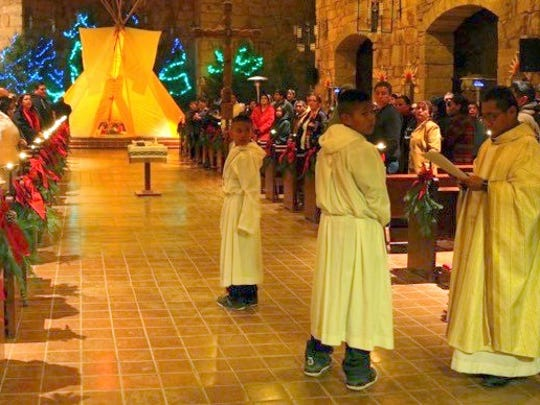 The priest and altar boys prepare for the Christmas Eve Mass at St. Joseph Apache Mission.