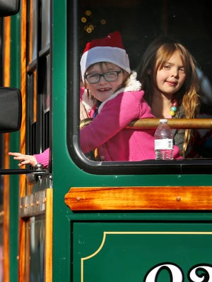 Girls peek out from a trolley during the Noblesville Christmas Parade, Sunday, Nov. 26, 2017.