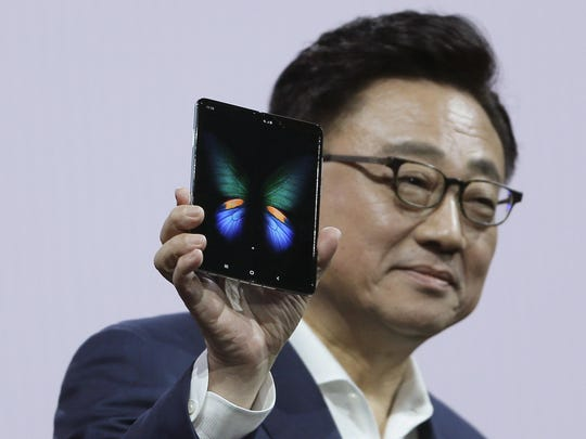 DJ Koh, President and CEO of IT and Mobile Communications, holds up the new Samsung Galaxy Fold smartphone during an event Wednesday, Feb. 20, 2019, in San Francisco.