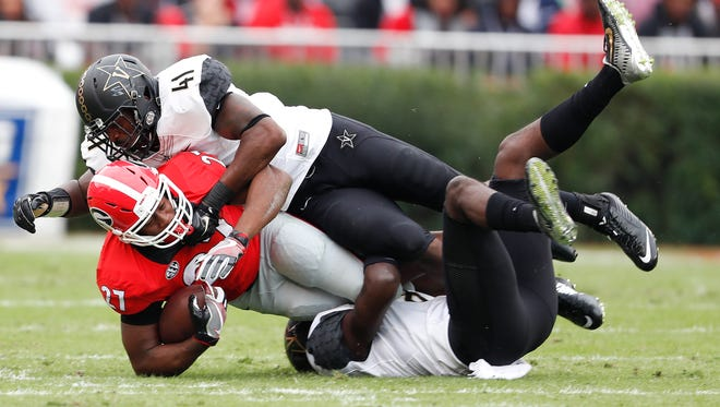 Georgia running back Nick Chubb (27) is brought down by Vanderbilt 's Joejuan Williams (8) and Zach Cunningham (41) in the first half on  Oct. 15, 2016.