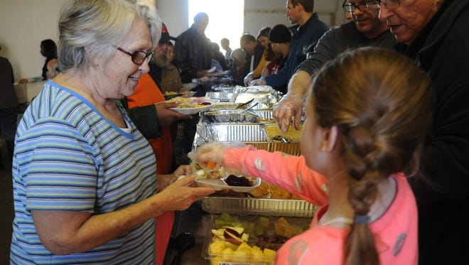 Lynne Page receives a meal at the Fieldhouse for the Homeless on Thanksgiving Day.