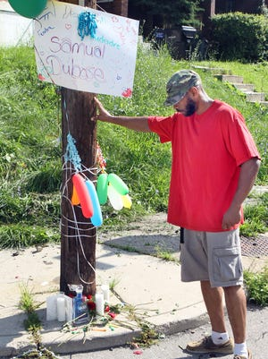 Jabari Dailey, 43, who has been friends with Samuel Dubose since childhood, pauses at an impromptu memorial at Valencia and Rice streets in Mount Auburn, where Dubose was shot and killed by University of Cincinnati police officer Ray Tensing during a traffic stop Sunday.