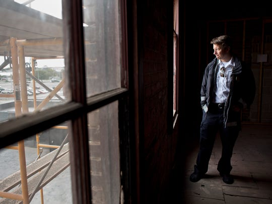 Port Huron Fire Captain Corey Nicholson looks out a window while touring the building with owner Larry Jones Tuesday, October 13, 2015 at 230 Huron Avenue in downtown Port Huron. The project to bring 8 loft units and ground floor retail space is scheduled to be completed by January.