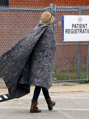A patient walks to patient registration with her free blanket Saturday at the Remote Area Medical clinic at Milton High School. Patients received free medical, dental and vision services as well as free hair cuts.