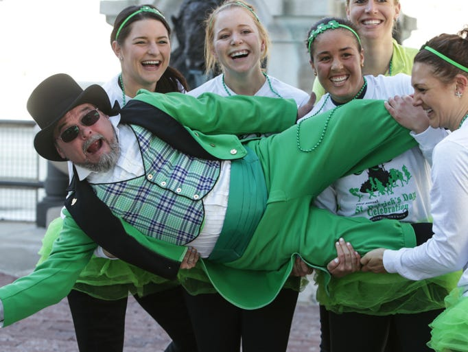 Official leprechaun, Michael McCrackin gets a lift by costume contest second place runners. Shamrock Runners gathered on Monument Circle for the 23rd, annual Shamrock Run 5k.