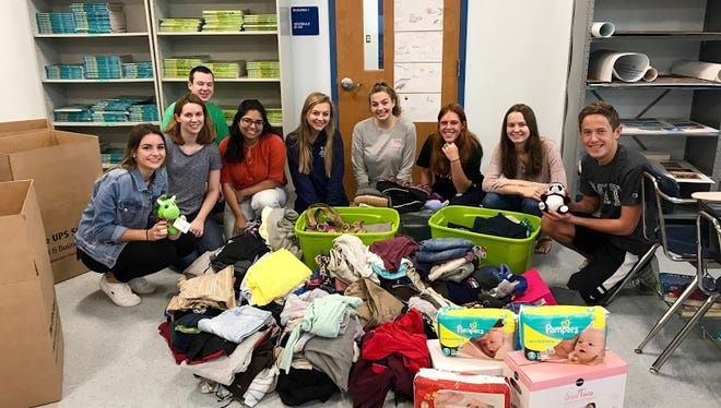 Sala Hussein and Sandra Drmanovic, alongside members of their International Club, sit alongside donations brought in.
