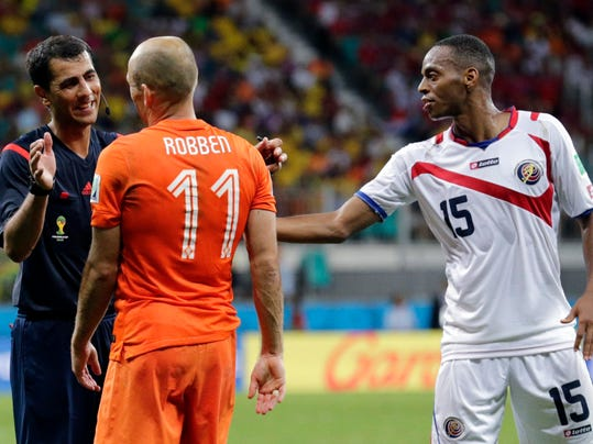 Netherlands' Arjen Robben speaks to referee Ravshan Irmatov from Uzbekistan after tripping over Costa Rica's Junior Diaz (15) during the World Cup quarterfinal soccer match at the Arena Fonte Nova in Salvador, Brazil, Saturday, July 5, 2014. (AP Photo/Wong Maye-E)