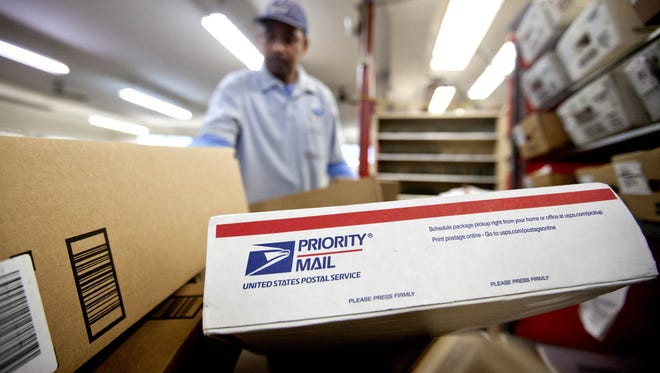 In this 2013 file photo, packages wait to be sorted in a Post Office as U.S. Postal Service letter carrier  Michael McDonald, gathers mail to load into his truck before making his delivery run, in Atlanta.