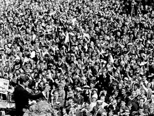 President John F. Kennedy, left, waves to crowd gathered