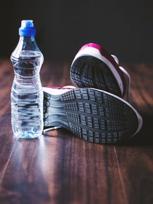 Sport equipment. Sneakers and water wooden background