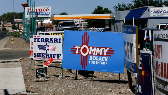 Campaign signs for Republican sheriff candidates Shane Ferrari and Tommy Bolack are situated Wednesday at the intersection of East 20th Street and East Main Street in Farmington.