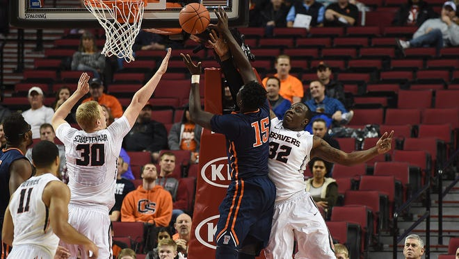 Oregon State's Jarmal Reid (32) and Olaf Schaftenaar defend a shot by Cal State Fullerton's Jamar Akoh in Friday's Far West Calssic Invite game at the Moda Center.