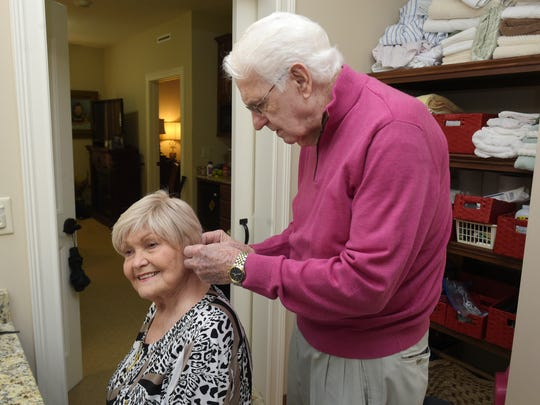 Clifford Smith helps his wife, Wilma, put on her earrings