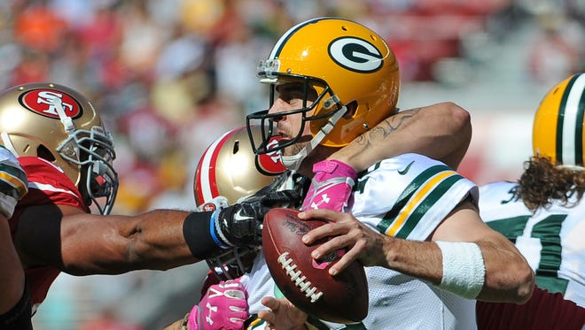 Green Bay Packers quarterback Aaron Rodgers (12) unloads a left handed pass to avoid a sack in the second quarter against the San Francisco 49ers at Levi's Stadium.
