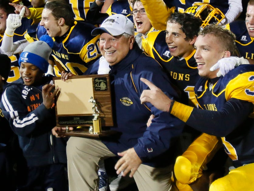 South Lyon football coach Mark Thomas holds the district championship trophy after a 17-7 win over Plymouth Canton on Oct. 17, 2014.