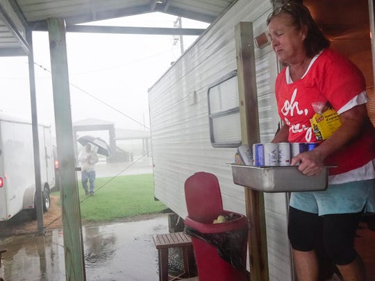 Lisa Broussard of Abbeville removes items from her trailer as early rain squalls from Hurricane Harvey in Holly Beach, La. Friday, August 25, 2017.