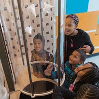 Kids try out the vertical flyer station at Discovery World's Physics & You exhibit