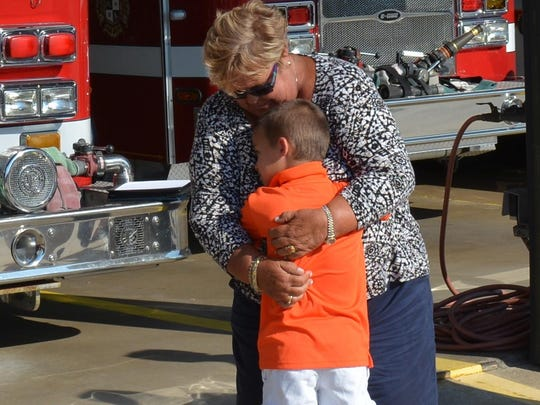 Jenny Mama hugs her 7-year-old nephew, Mason Farr, at the Ocean City Fire Department. Farr is being recognized for helping his aunt after she suffered a spinal cord injury while on a water slide.