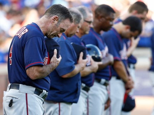 Members of the Minnesota Twins including manager Paul Molitor observe a moment of silence, in remembrance of the people killed and injured in Dallas, before a baseball game against the Texas Rangers at Globe Life Park, Friday, July 8, 2016, in Arlington, Texas. (AP Photo/Jim Cowsert)