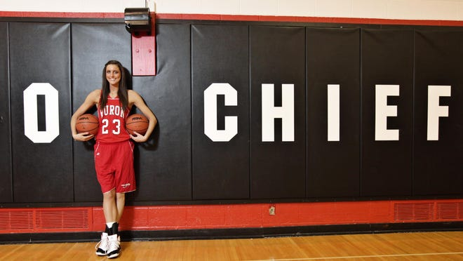 """Basketball All-Stater Kiara Kudron stands in front of """"Go Chiefs"""" logo in the gymnasium at New Boston Huron High School in 2014."""