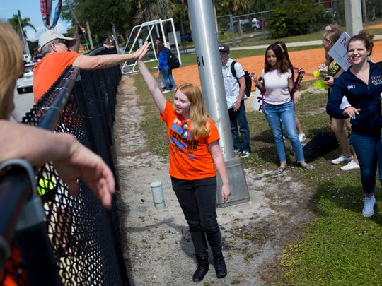 Michaela O'Brien, 15, a sophomore at Naples High School, high-fives one of the supporters who showed up outside the school to support the students at Naples High School during a walkout on the 19th anniversary of the Columbine shooting Friday, April 20, 2018 in Naples.