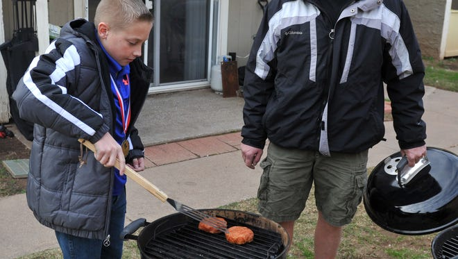 Nicholas Tant, 11, prepares to flip grilled pork chops as his dad, Charles, supervises. Nicholas has won awards for his cooking, including first place at the Possum Kingdom Steak Association's Kid's Division cook-off.