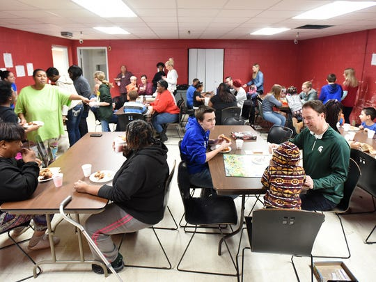The dining room at Genesis House II in Detroit is busy with residents and volunteers March 18 during a game night sponsored by the Caleb White Project.
