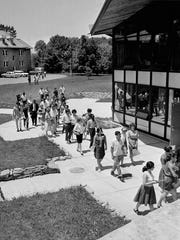 In this June 24, 1964 photo, black and white students attending an indoctrination course before going to Mississippi to aid in black voter registration and education for summer, walk across the campus of Western College for Women where the classes are being held in Oxford, Ohio.