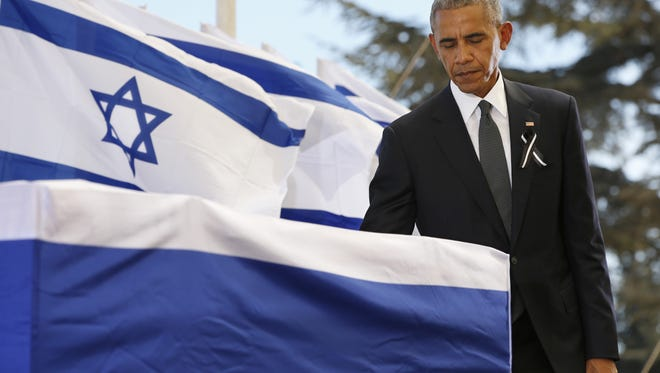 President Obama touches the coffin of Shimon Peres after delivering his eulogy during the funeral at Mount Herzl Cemetery on Friday in Jerusalem.