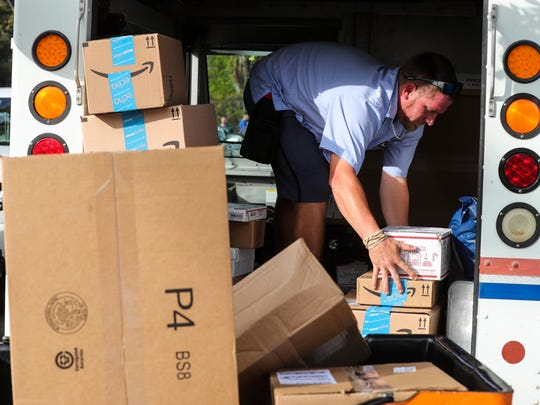Letter carrier Mike Kelly loads large packages into his truck as he starts his busy day. Monday marks the busiest day for the United States Postal Service of the year. Couriers were busy packing up their trucks to begin the day's deliveries.
