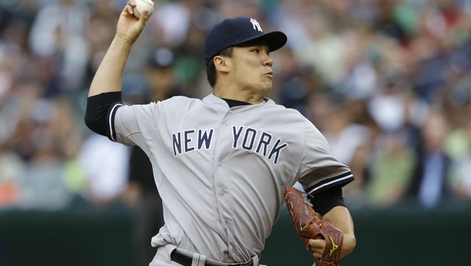 Yankees starting pitcher Masahiro Tanaka throws against the Seattle Mariners in the first inning of  Wednesday night's game in Seattle.