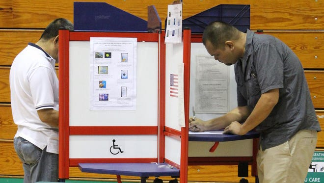 In this file photo, residents cast their votes in the General Election at the University of Guam Calvo Field House in Mangilao on Nov. 4, 2014. Citizen for Public Accountability hope to repeal recent pay raises for elected officials via a referendum on this year's General Election ballo.
