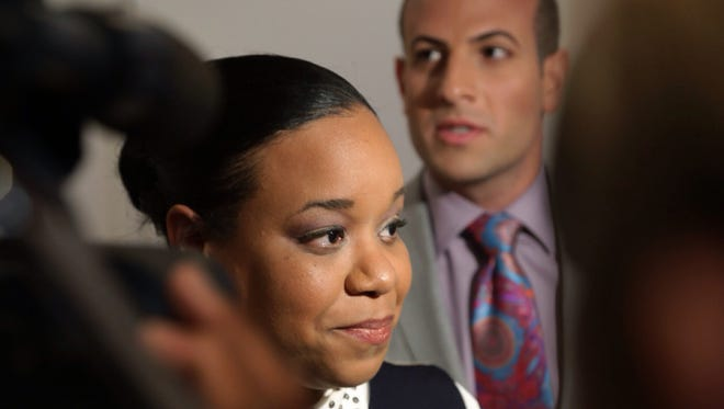Pershing High teacher Tiffani Eaton-Davis, who was fired for using a broom to break up a fight in her classroom, stands with her lawyer Jeffrey Lance Abood while speaking during a news conference at Abood Law Firm in Birmingham on May 14, 2014.