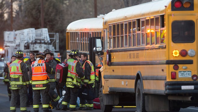 Fire department personnel work at the scene of an accident involving an SUV, a truck and a Poudre School District school bus in the 500 block of N. Taft Hill Road Tuesday, January 5, 2016. Minor injuries were reported among the drivers and the 31 children on the bus.