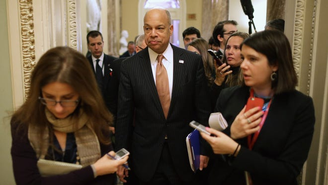 Homeland Security Secretary Jeh Johnson is surrounded by reporters as he moves between meetings with senators at the U.S. Capitol on Feb. 3 in Washington.
