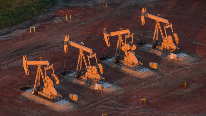 Pumpjacks are seen in an aerial view in July 2013 near Watford City, N.D. North Dakota has seen a boom in oil production thanks to new drilling techniques including horizontal drilling and hydraulic fracturing. Dakota Access LLC, a unit of Energy Transfer Partners, proposes to transport up to 570,000 barrels of light sweet crude oil daily from North Dakota's Bakken oil fields through Iowa to Patoka, Ill.