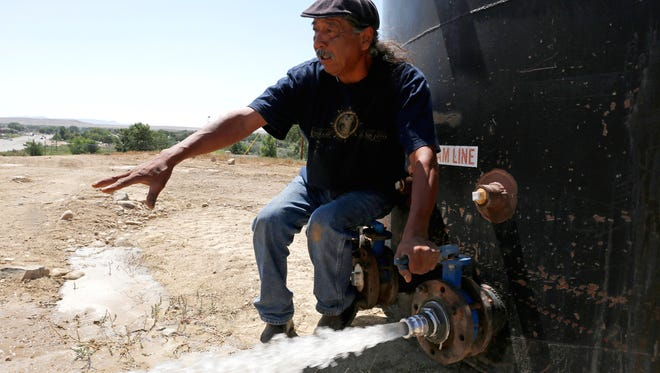 In this Aug. 18, 2015, file photo, Joe Ben Jr., a Shiprock Chapter House Farm Board representative, tests the water from tanks at the Chief Hill location in Shiprock, N.M. The U.S. Environmental Protection Agency said new tests on emergency water sent to Navajo Nation farmers after the Gold King Mine spill indicate the water met federal and tribal standards for livestock and irrigation.
