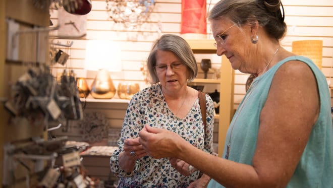 Fleming Markel, founder of the Greenville Ten Thousand Villages store, looks at ornaments with customer Gloria Henley of Six Mile on Friday, September 16, 2016.