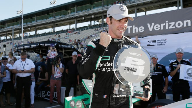Simon Pagenaud, of France, poses with his trophy after winning the pole position for the IndyCar auto race Saturday, Sept. 17, 2016, in Sonoma, Calif.